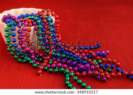 Holiday beads flowing out of a white bowl onto a red tablecloth