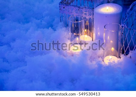 Holiday greeting card and candles in snow