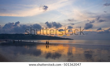 Holiday makers at Jimbaran Beach in Bali, Indonesia, at sunset.