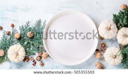 Holiday table decoration with white decorative pumpkins, thuja branches, walnuts, acorns and empty dinner plate over white wooden background. Top view with space for text