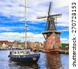 Holland, Haarlem' canals. view with traditional windmill and sai - stock photo