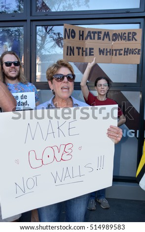 HOLLYWOOD, CA - NOVEMBER 13 2016: A protester shouts and holds a sign  denouncing Donald Trump's plan to build a wall during a rally on November 13, 2016 in Hollywood, California.