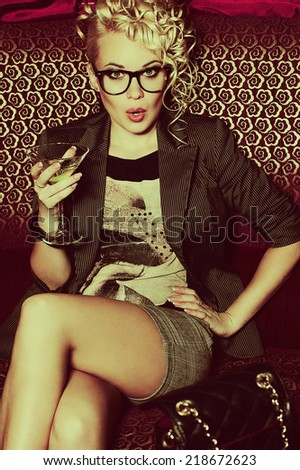 Hollywood celebrity concept. Gorgeous young superstar drinking cocktail disturbed by paparazzi in the night club (lounge bar). Luxurious look and accessories. Hipster style. Indoor shot