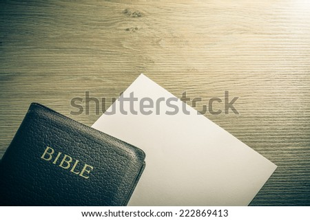 Holy Bible and a sheet of paper on a wooden table. Background concept with large copy space available. / Bible and paper background