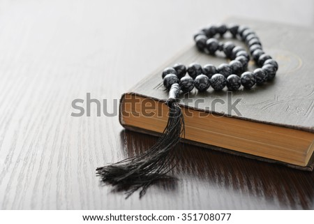 Holy Quran with beads over wooden background closeup. Small shallow DOF.