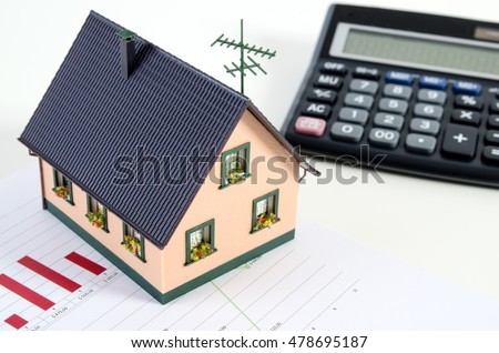 Home finances or saving for a house. House miniature and calculator