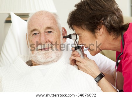 Home health nurse checking her senior patient's ears with an otoscope.