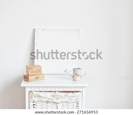 Home interior decoration with canvas, watering can and wooden boxes on the bedside table