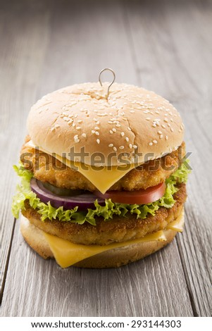 Home made chicken burger with cheese, lettuce, tomato and onion on wooden board