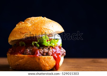 home made hamburger with meat, salad, onion, tomato and ketchup
