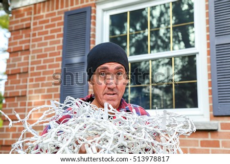 Home owner  looks dubious as he begins the annual chore of putting up the lights