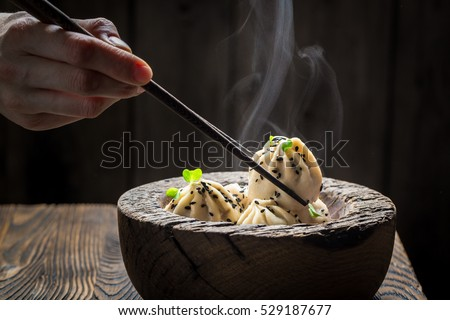 Homemade and hot manti dumplings in wooden bowl