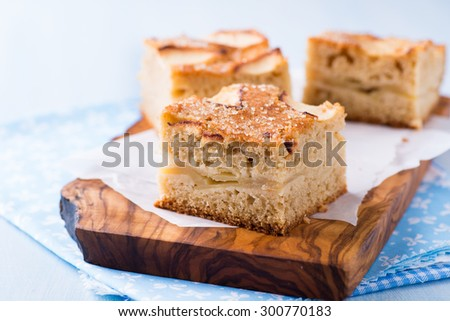 Homemade apple cake, traybake, slices on olive wood background, closeup, selective focus