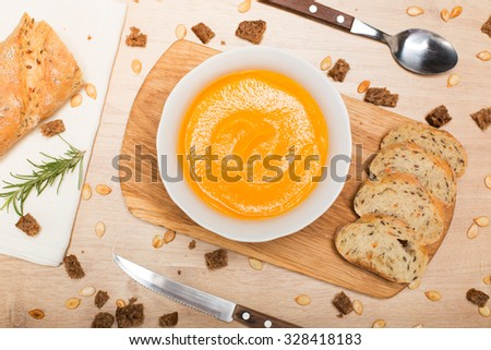Homemade Autumn pumpkin cream Soup with Bread top view