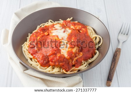 homemade breaded cutlet in tomato sauce and melted cheese over spaghetti in brown bowl on white background
