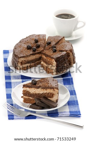 Homemade chocolate cake in white plates and coffee on blue che�ked napkin.