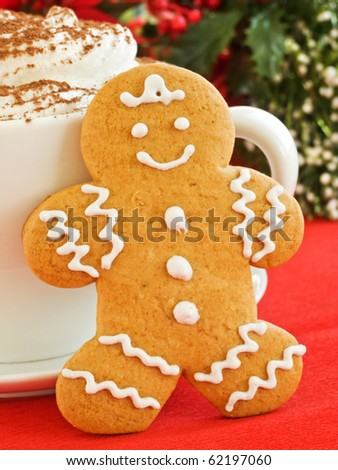 Homemade gingerbread man cookie and cup of chocolate with whipped cream. Shallow dof.