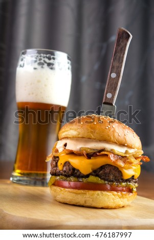 Homemade gourmet beef burger with glass of beer and steak knife