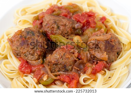 Homemade meatballs in sauce on a bed of fettuccine ribbon pasta