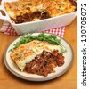 Homemade moussaka served with rocket salad. - stock photo