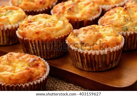 Homemade muffins with chicken and cheese on brown wooden board.