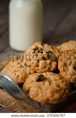 Homemade Oatmeal Raisins Biscuits in metal tray with milk bottle in background