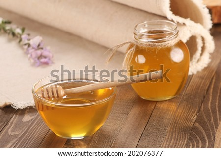 honey in a glass bowl on a wooden boards background and napkins made of coarse cloth