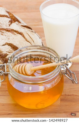 honey with bread and milk on wooden table