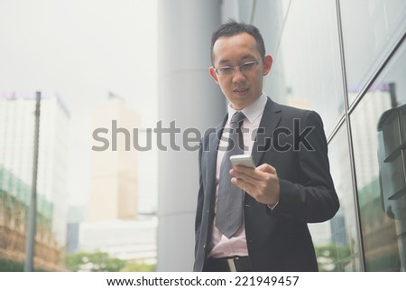 hong kong businessman in busy central district, light vintage blue tone applied