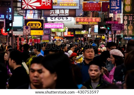 HONG KONG, CHINA - FEB 8: A crowd of people walking on night city under advertising signs, billboards, neon signs. Focus on signs on February 8, 2016. There are 1,223 skyscrapers in Hong Kong.