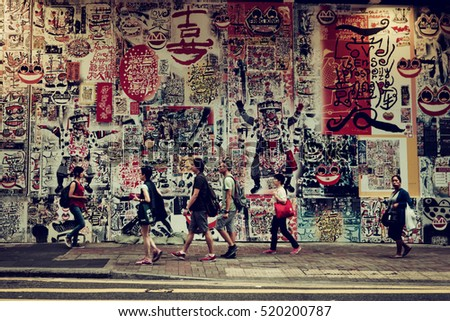 Hong Kong - October 2016: People walking in front of wall with colorful drawings. Retro look.