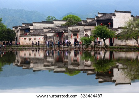HONGCUN, CHINA - APRIL 20: Tourists walking around Moon Lake in Hongcun Village, China on April 20, 2014. Hongcun is ancient village in Anhui Province, near the southwest slope of Mount Huangshan.