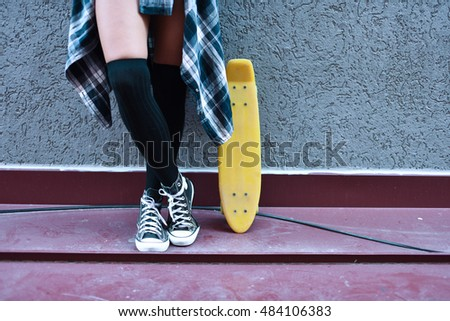horizontal image of a female's legs standing leaned on a gray wall with her legs crossed, wearing knee high stockings, sneakers and plaid shirt with a yellow skateboard upward next to her