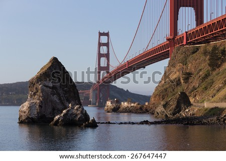 Horizontal image of big sea rocks near Golden Gate bridge with old lighthouse and fog station under the bridge in soft morning light. San Francisco. California. USA