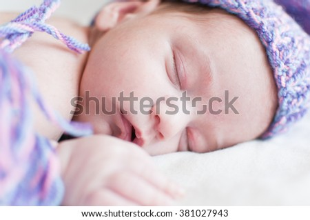 Horizontal portrait of the sleeping baby in purple hat