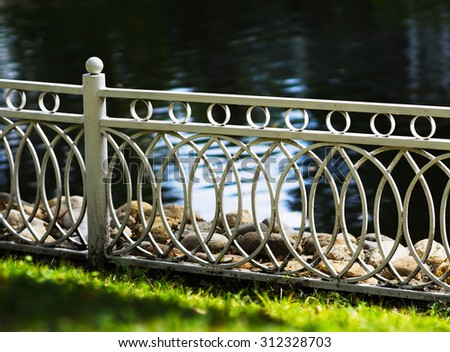 Horizontal white pond fence in park bokeh background