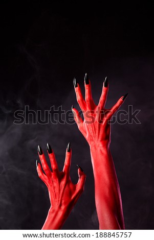 Horror red devil hands with black nails on smoky background, studio ...