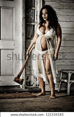 Horror Scene of a Pregnant Woman holding an Axe at front door of an old house