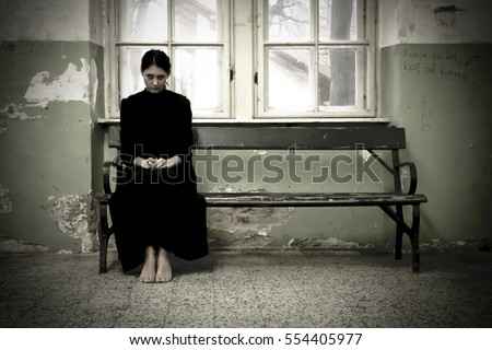 Horror scene of a scary woman. Woman in black dress sitting on the bench in demolished room
