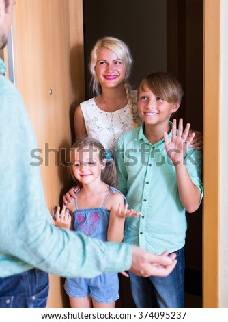 Hospitable man greeting happy smiling guests at apartment entrance