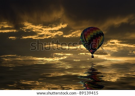 Hot air balloon floating over a lake at sunset.