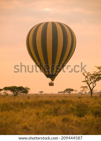 Hot air balloon landing in african savannah