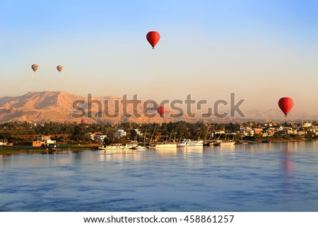 Hot air balloons floating over the Nile River in Luxor at sunrise