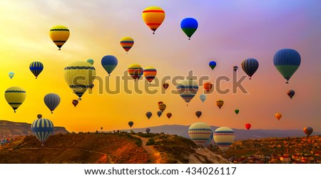 Hot air balloons landing in a mountain Cappadocia Goreme National Park Turkey.