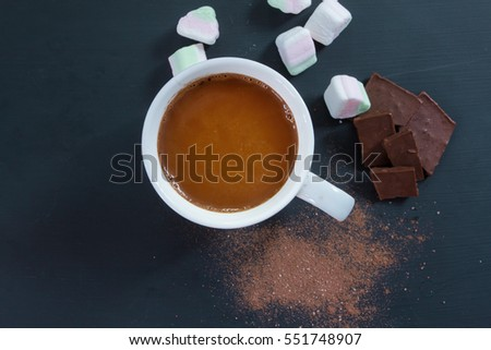 Hot chocolate in a cup, with chocolate on black background, top view