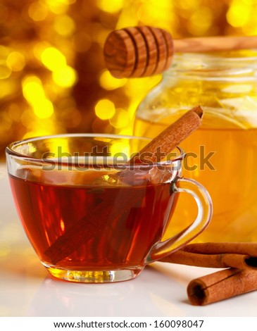 Hot christmas drink with cinnamon sticks and honey with wood stick