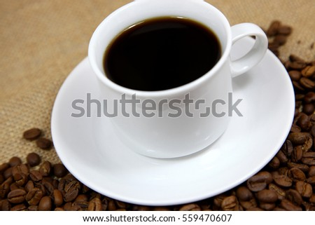 Hot coffee with a background of coffee beans