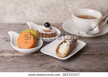 Hot Cup of Tea with Decadent Desserts on Rustic Board