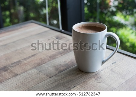 hot fresh chocolate coffee in white glass on wooden table nature view at sunset at coffee time / hot fresh coffee