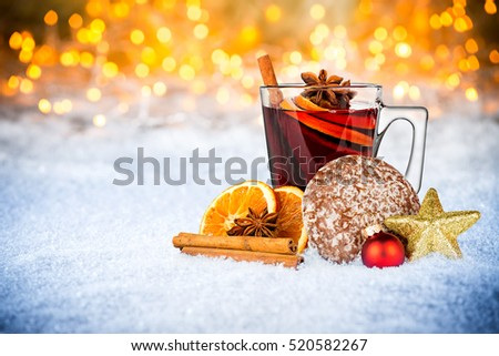 hot mulled spiced red wine in glass mug with gingerbread orange slice christmas xmas decoration illuminated bright lights bokeh background